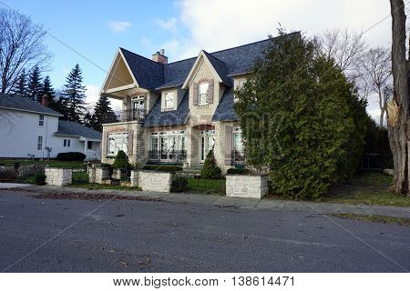An elegant home with a cedar tree (Thuja occidentalis) on East Bluff Drive in Harbor Springs, Michigan.