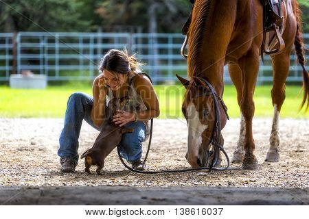 Farm girl talking on phone with horse and dog