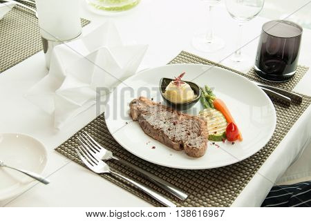 beef steak with sear marks with asparagus and red carrot garnish.
