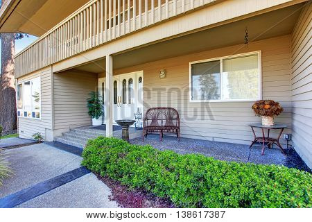 View Of Cozy Porch With Concrete Walkway And Trimmed Hedges.