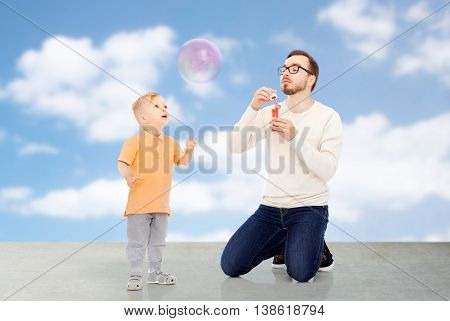 family, childhood, fatherhood, leisure and people concept - happy father and little son blowing bubbles and having fun over blue sky and clouds background
