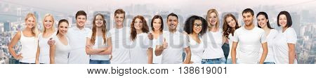 diverse, gesture and people concept - group of happy different body size and age and gender people in white t-shirts hugging showing thumbs up over city background