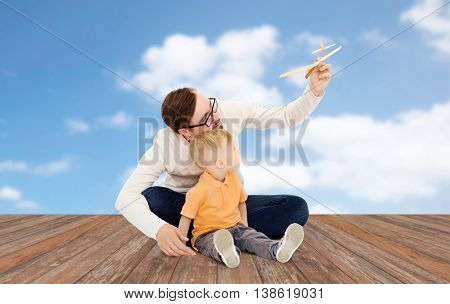 family, childhood, fatherhood, leisure and people concept - happy father and little son playing with toy airplane over blue sky and clouds background