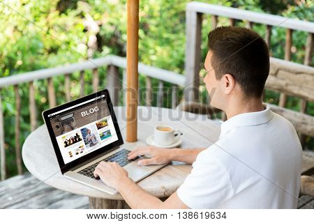 business, people, mass media, internet and technology concept - close up of businessman with blog web page on laptop computer screen drinking coffee on summer terrace