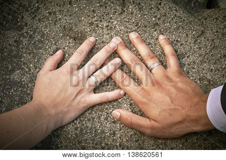 View of newlyweds hands with rings on stone