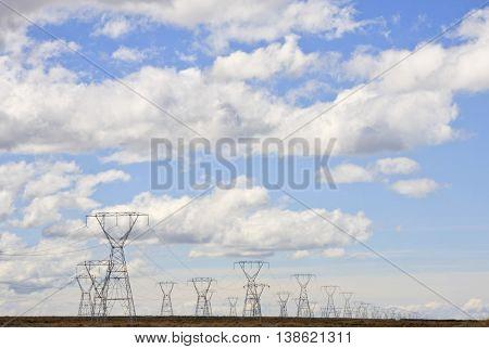 Power pylons set against a cloudy blue sky