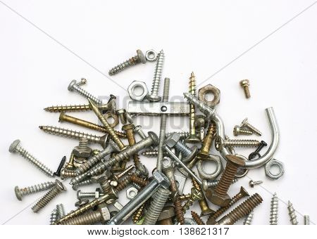 A pile of nutsbolts screws and other fasteners on a white background