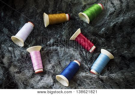 Sewing background. Accessories for needlework. Colorful bobbins on black fabric background.