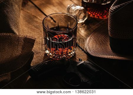 Glass of whiskey, revolver and hat on a wooden table