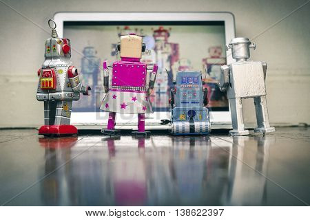 4 robot toys watching a film on a laptop computer