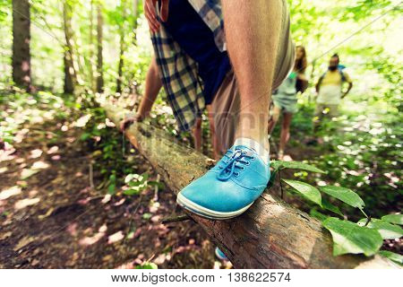 adventure, travel, tourism, hike and people concept - close up of man climbing over fallen tree trunk in woods