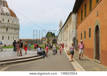 Pisa Italy - June 29 2015: Tourists walking on Piazza del Duomo in historic centre. Province Pisa Tuscany region of Italy