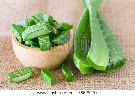 Aloe useful herbs cut into pieces put on sackcloth background.