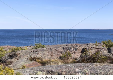 View from a cliff in the archipelago, Aland, The Baltic Sea. Rocks, cliffs and vegetation on the shore. Red granite.