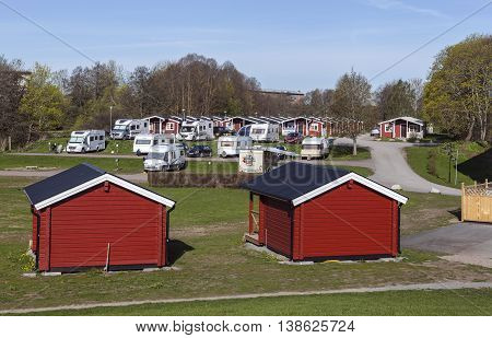 UPPSALA, SWEDEN ON MAY 06, 2016. View of lodges, caravans and campers in Fyrishov camping. Red small building. Morning Editorial