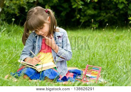 clever little pupil reading a book on the nature
