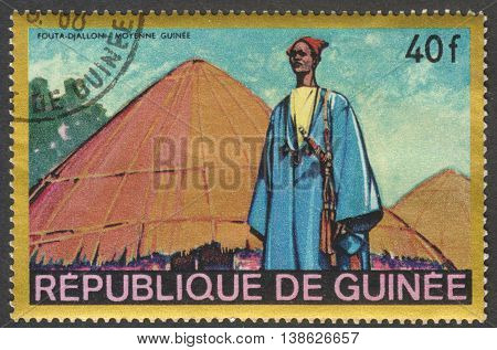 MOSCOW RUSSIA - CIRCA FEBRUARY 2016: a stamp printed in GUINEA shows a scene of traditional native life the series