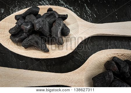 Two tablespoons with black garlic cooking ingredients