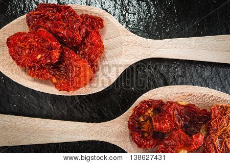 Two tablespoons  with dried tomatoes cooking ingredients