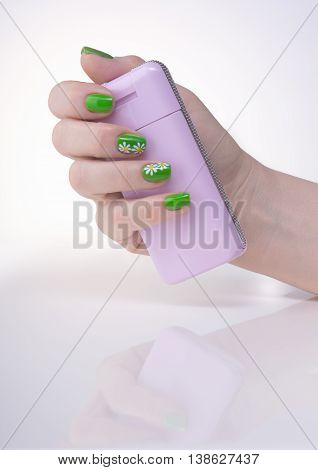 Female left hand with green manicure on a white table