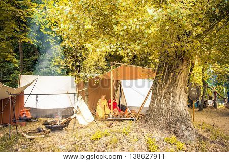 Monterenzio Italy 09 July 2016 - two women rest under a big sequoia tree in the woods during a Celtic historic reenactment