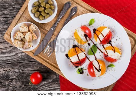 tomato mozzarella basil caprese salad on white dish on cutting board with vintage fork and knife fitness ciabatta croutons and green olive close-up