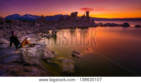 Woman Relaxing Looking at Beautiful Sunset over calm water of Mono Lake