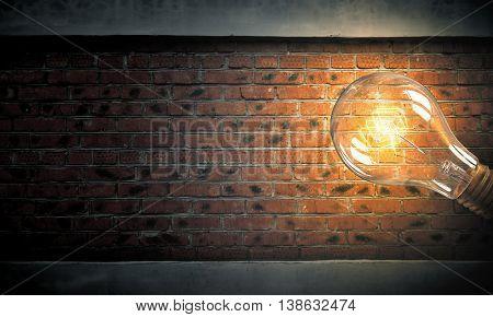 Light bulb on brick surface . Mixed media