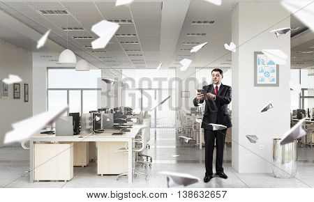 Businessman with tablet in hand . Mixed media