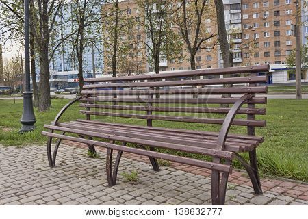 An empty bench on the boulevard. Behind the park the road and houses