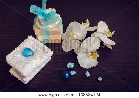 Spa setting in white and blue colors with different kind of natural soaps, soft towels and orchid on dark wooden background. Tower stack of different handmade soaps. Selective focus.