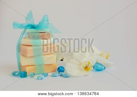 Spa setting in pastel and blue colors with different kind of natural soaps and orchid on white background. Tower stack of different handmade soaps on white. Selective focus. Copy space.