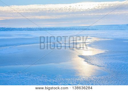 winter scenery with rising sun over the frozen lake