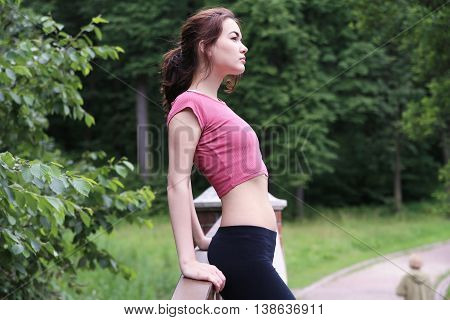 Profile portrait of happy young sporty woman relaxing in park. Female relaxing breathing fresh air outdoors.