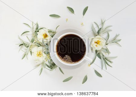 Cup of morning black coffee and white wild rose flowers on the wooden background; flat lay top view