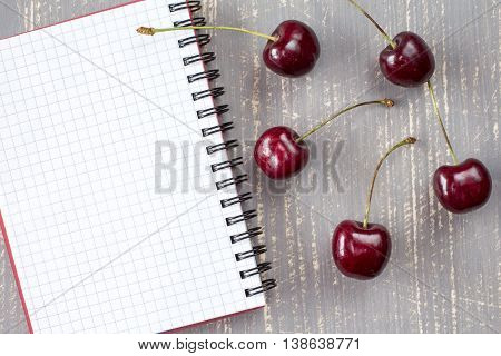Fresh Cherries And Blank Notebook.