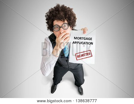 Disappointed Man Is Showing Document With Denied Mortgage Applic