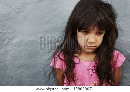 Unhappy Little Girl Standing Against Grey Wall