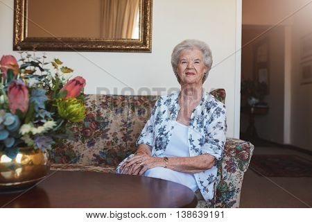 Indoor shot of beautiful senior woman sitting on a couch at old age home.