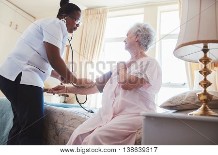 Female Nurse Checking Blood Pressure Of A Senior Woman