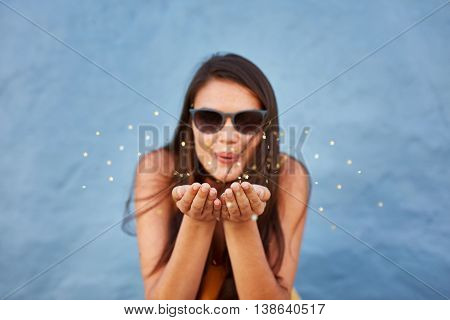 Close up shot of young woman blowing sparkles against blue background focus on hands of female model.