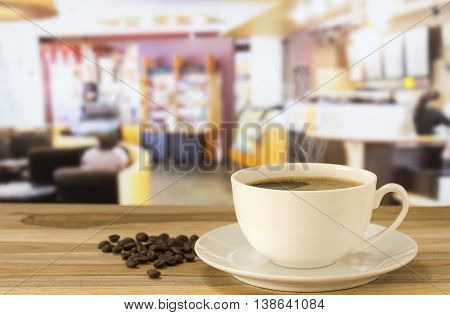 Coffee cup and coffee beans on table in cafe background. Space for your text.