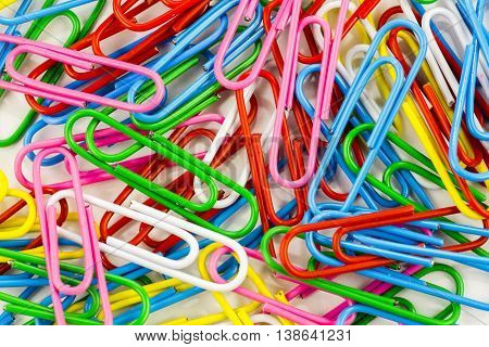 set of colored paper clips on a white background closeup