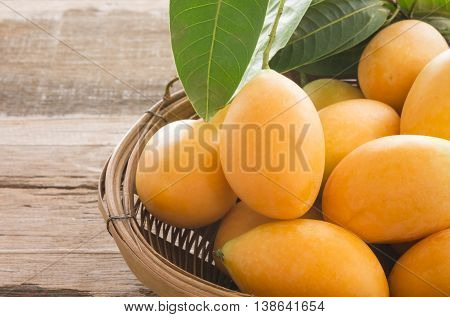 Closeup of ripe sweet marian plum ( Maprang Mayongchid Plum Mango) thai fruit on wooden table.