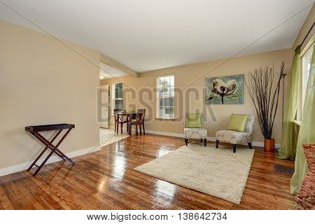Cozy Beige Sitting Room With Shiny Hardwood Floor And Dining Area
