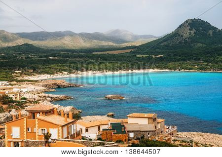 View of the Cala Agulla Beach in Mallorca island Spain. Beautiful landscape with Es Pelats village whitesand beach green hills and mountains