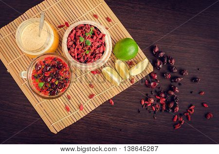 Fresh antioxidant herbal tea from dried goji berries, sweetbrier and blueberry in a glass cup on wooden background with lime and honey. Alternative medicine. Recovery.Rejuvenation. Slimming. Top view.