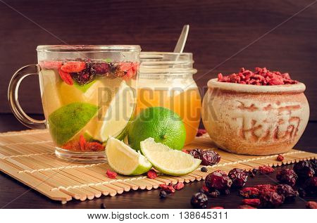 Fresh antioxidant herbal tea from dried goji berries, sweetbrier and blueberry in a glass cup on wooden background with lime and honey. Healthy food. Alternative medicine. Recovery. Slimming.