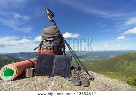 Camping in the mountains with a backpack on the background of blue sky.