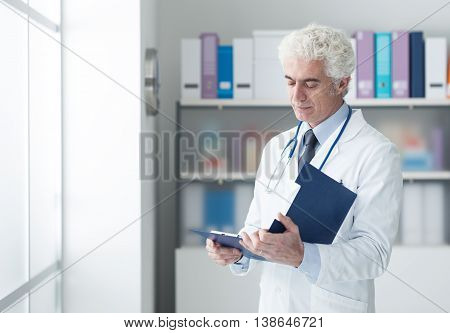 Confident doctor in the office checking medical records on a clipboard healthcare professionals concept
